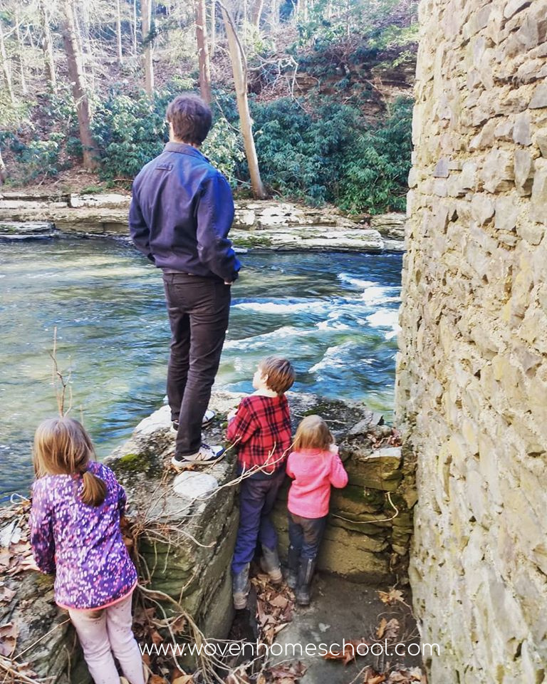 Three children overlooking a creek with their father