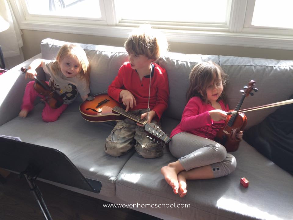 Three children sitting on the couch holding stringed instruments