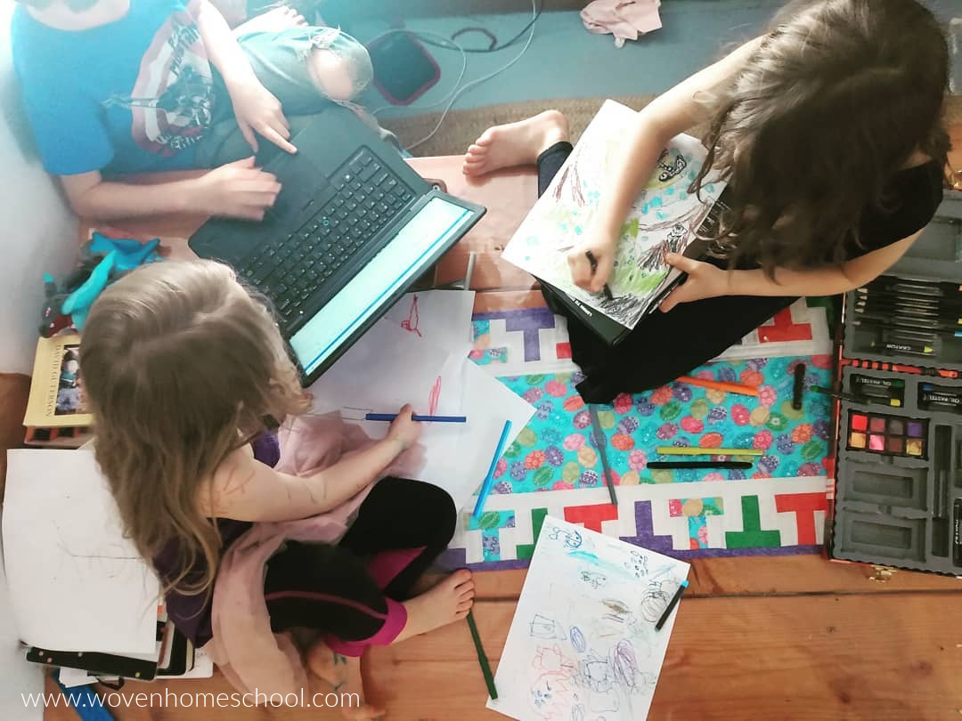Children coloring and typing at the kitchen table.