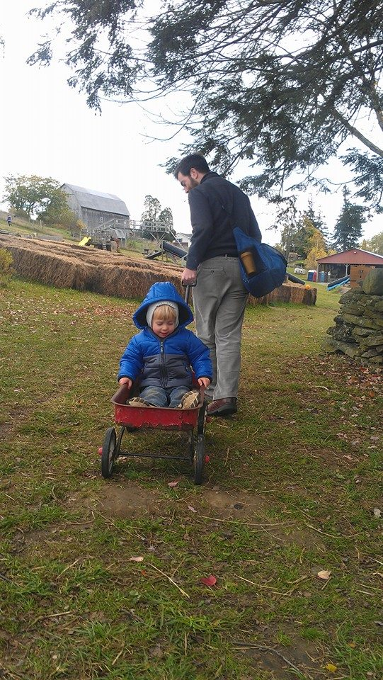 Child sitting in a wagon while his father pulls him.