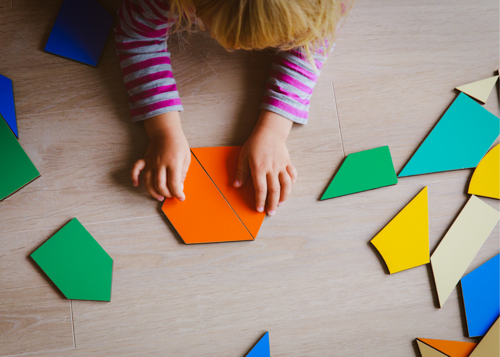 Child playing with shaped blocks on the floor.