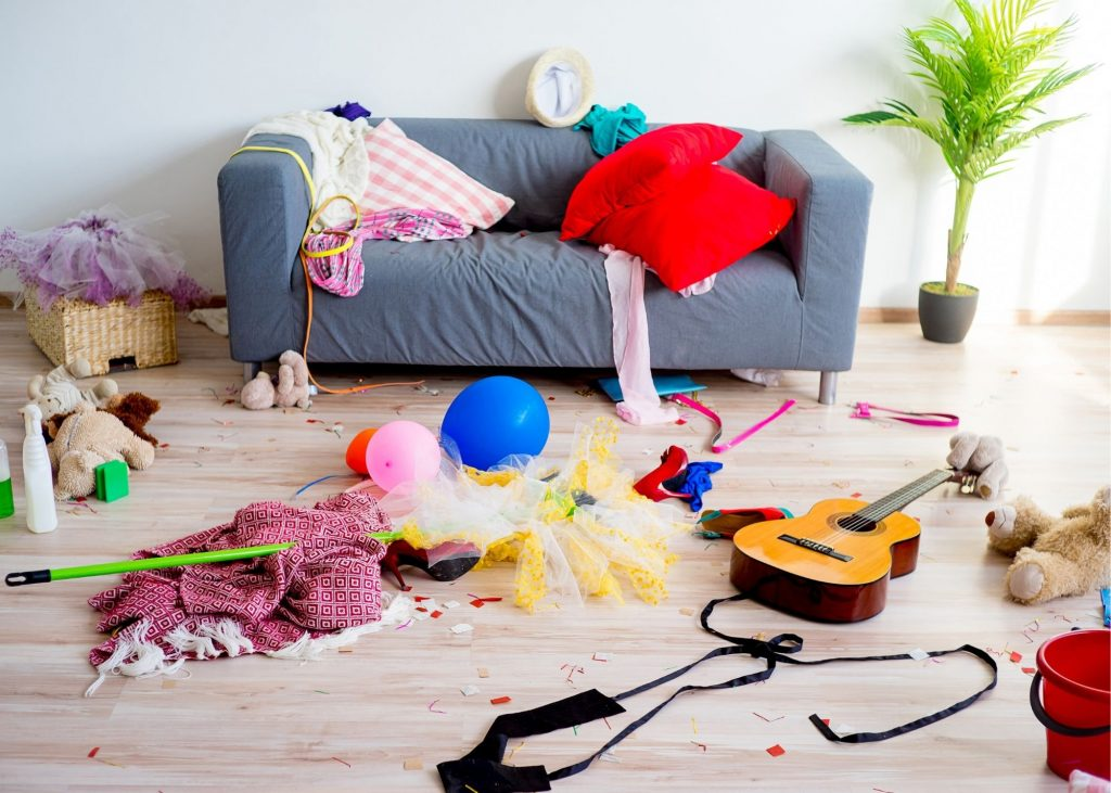 Room with blue couch and toys strewn on the floor